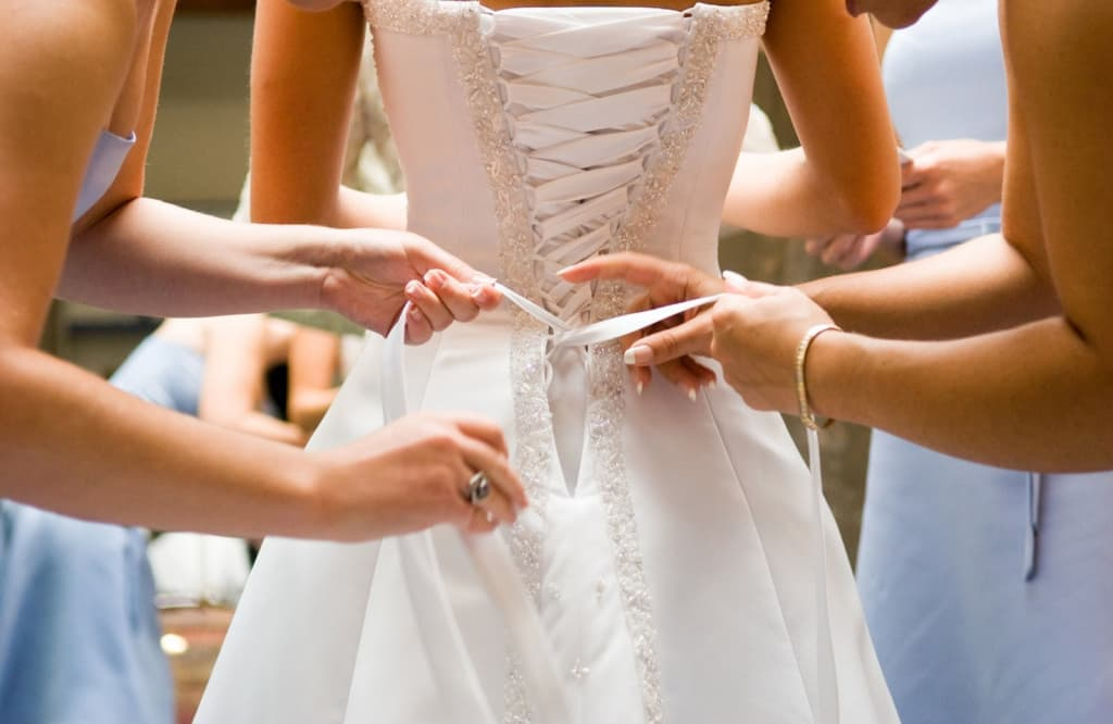 weddings-2012-12-women-tying-wedding-dress-main.jpg